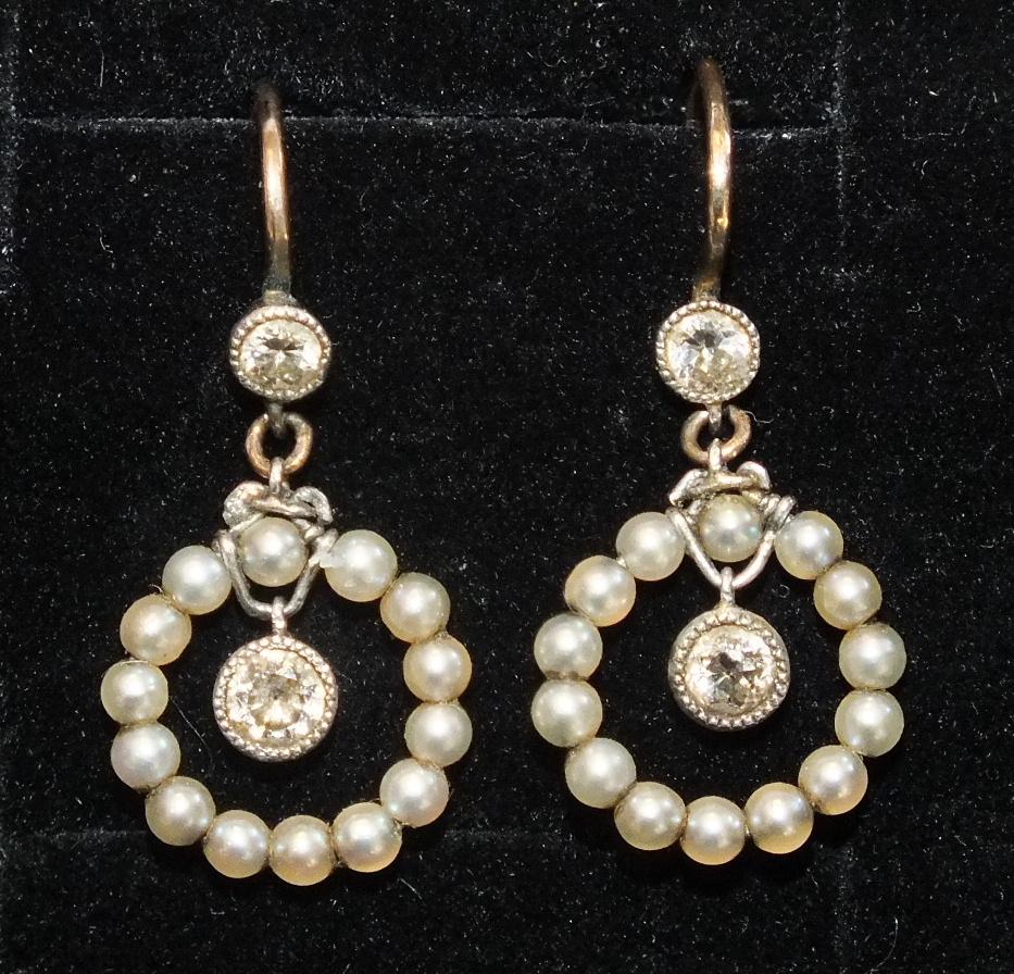 A pair of Edwardian pearl and diamond earrings, each millegrain-set an old brilliant-cut diamond