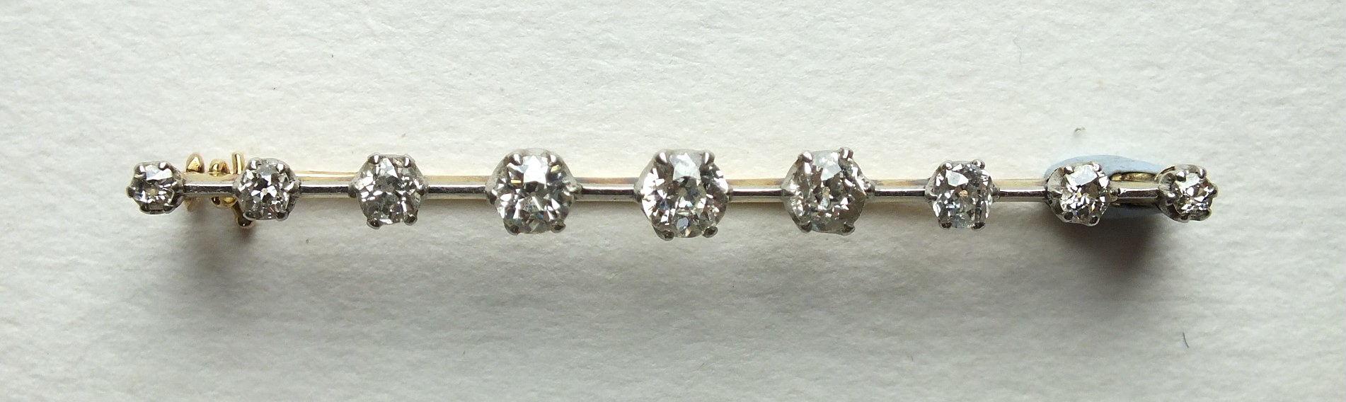An early-19th century bar brooch claw-set nine graduated old brilliant-cut diamonds, on a white