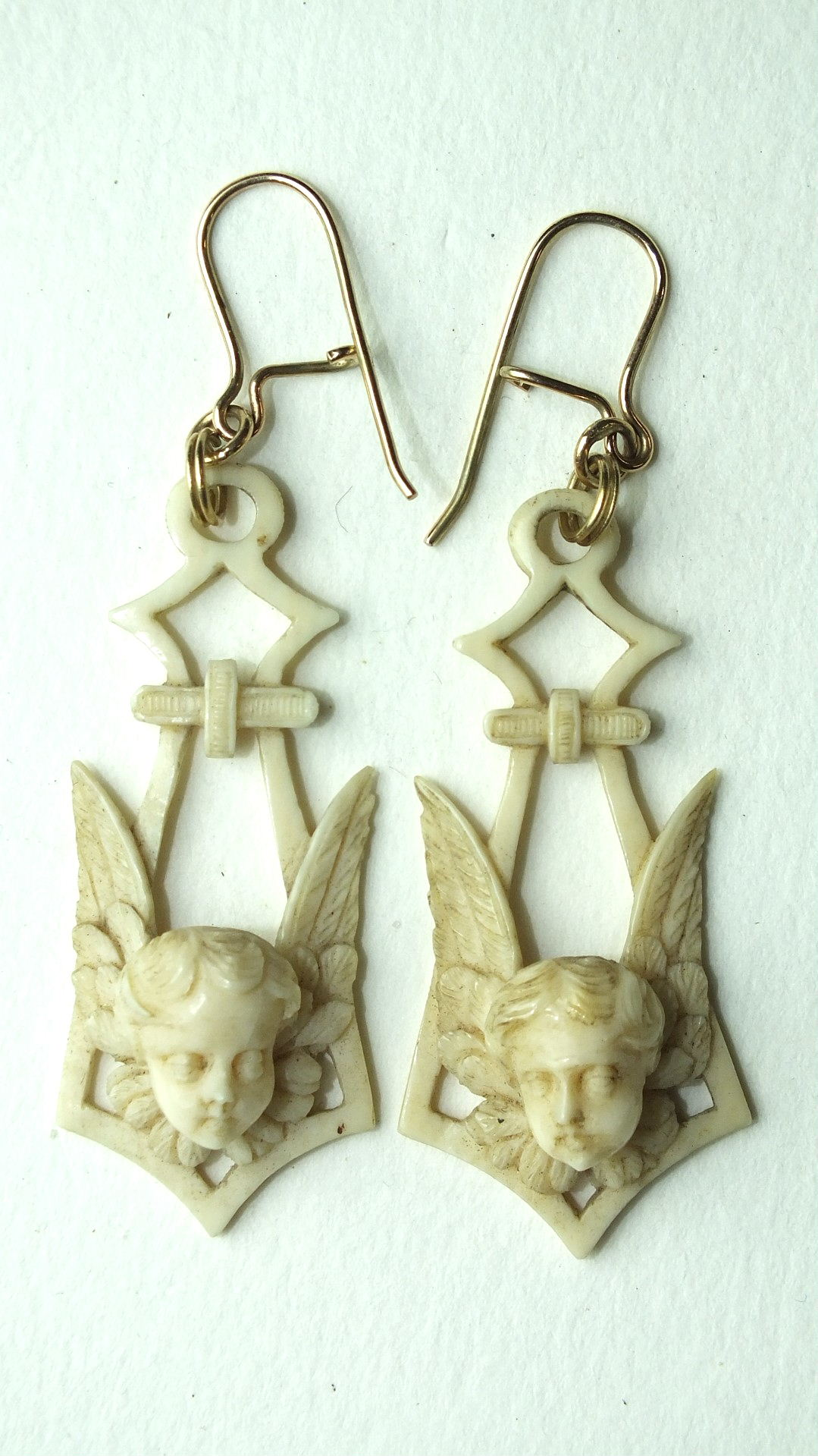 Lot 149 - A pair of Victorian ivory pendant earrings carved in the form of cherubs' heads and wings, later