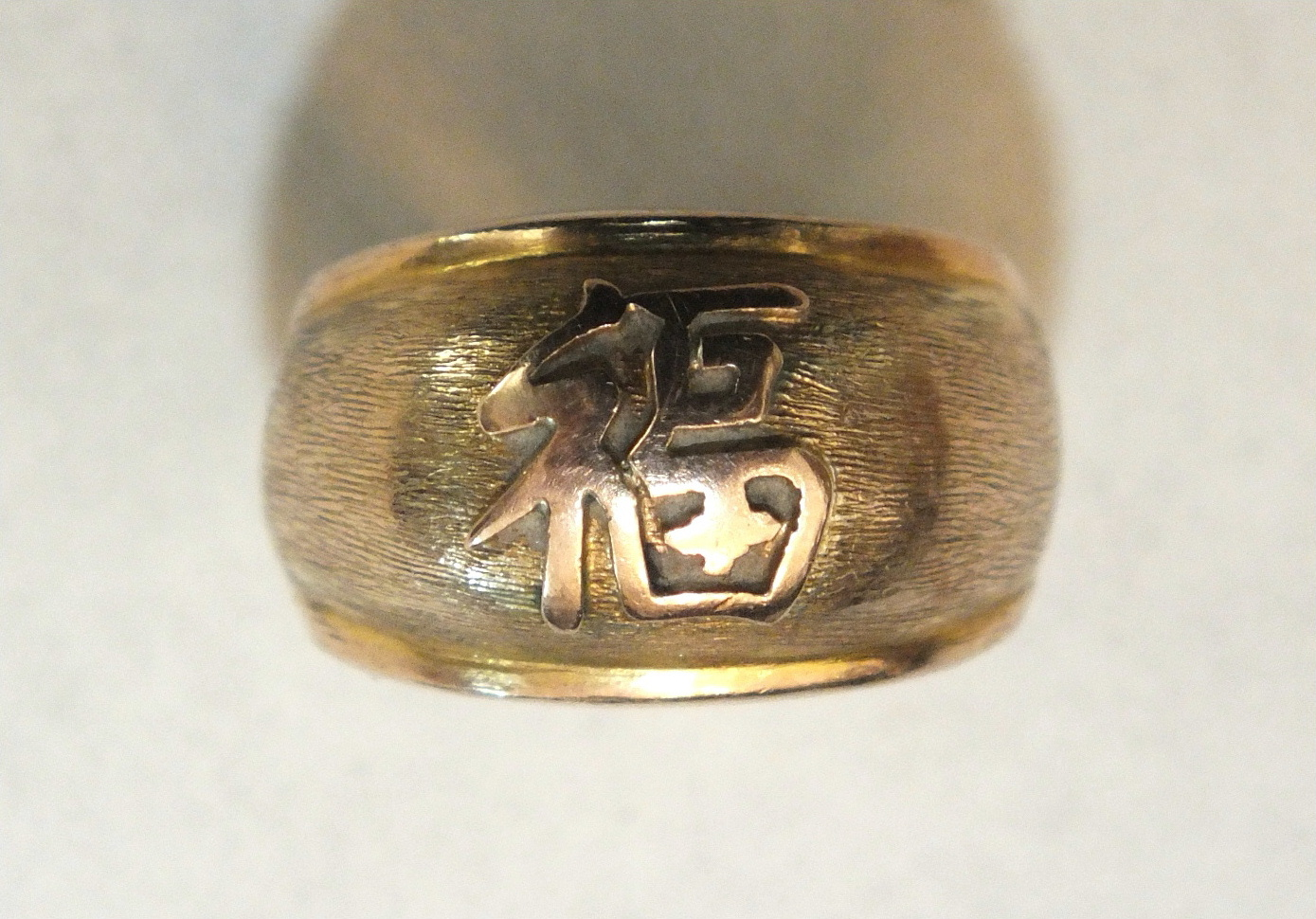 A gold ring with Chinese character, on textured ground, marked '14k', size L.