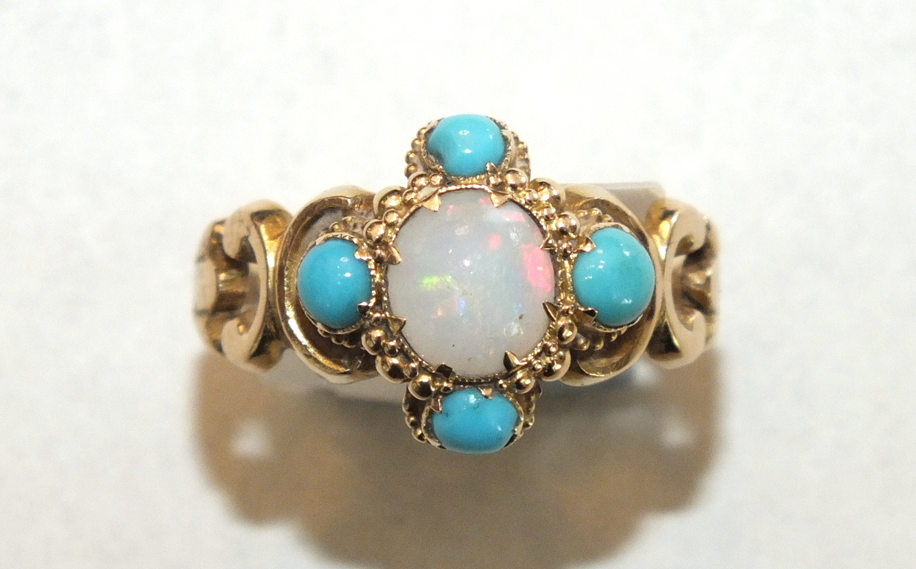 A 19th century ring set opal and turquoise cluster between scrolling shoulders, with engraved shank,