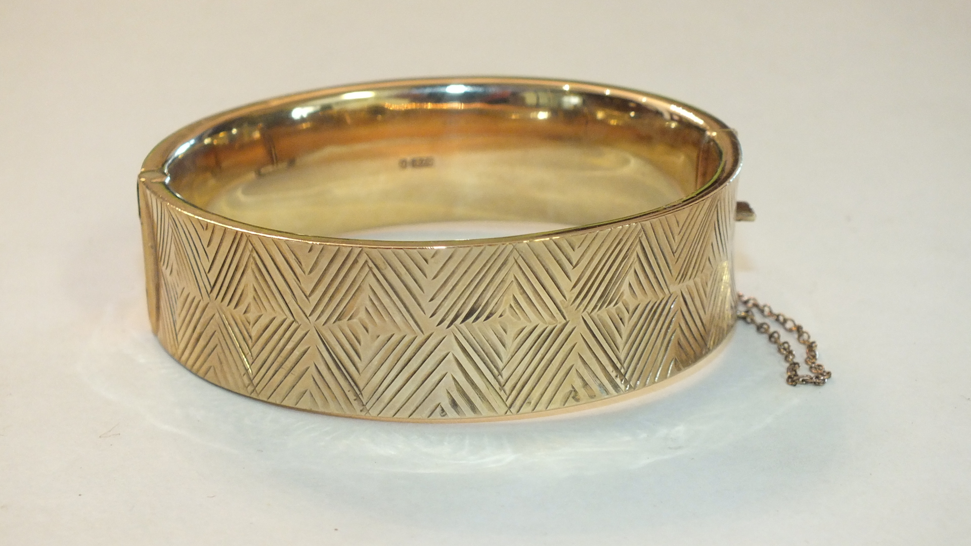 A 9ct gold hinged bangle with engraved geometric decoration, 27g.