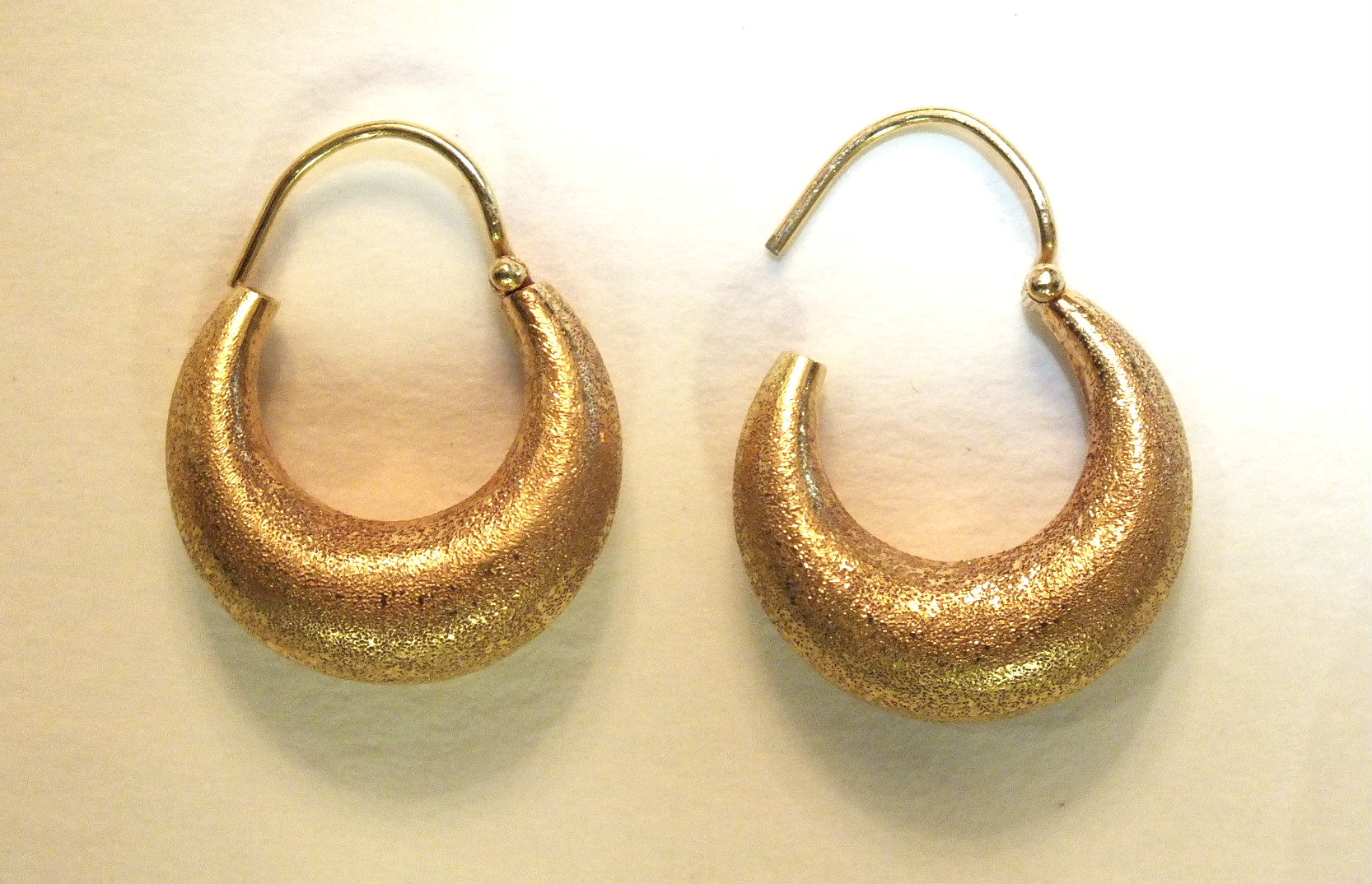 A pair of yellow metal hoop earrings with textured surface, unmarked, 4g.