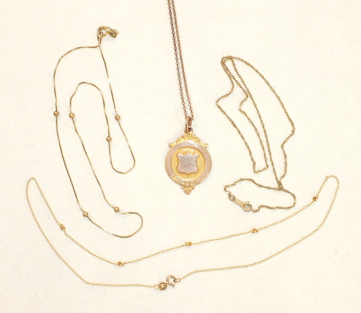 A 9ct gold medallion on chain and three other 9ct gold neck chains, 12.1g, (4).