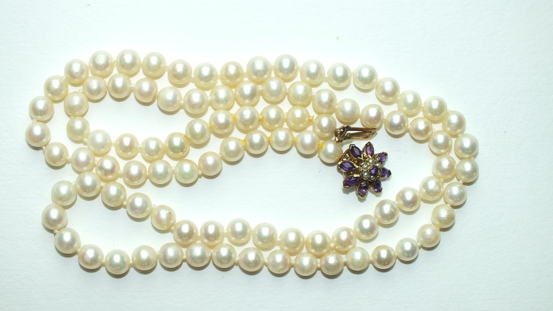 A long string of 95 uniform cultured pearls, 7mm diameter, with 9ct gold clasp set amethyst and seed