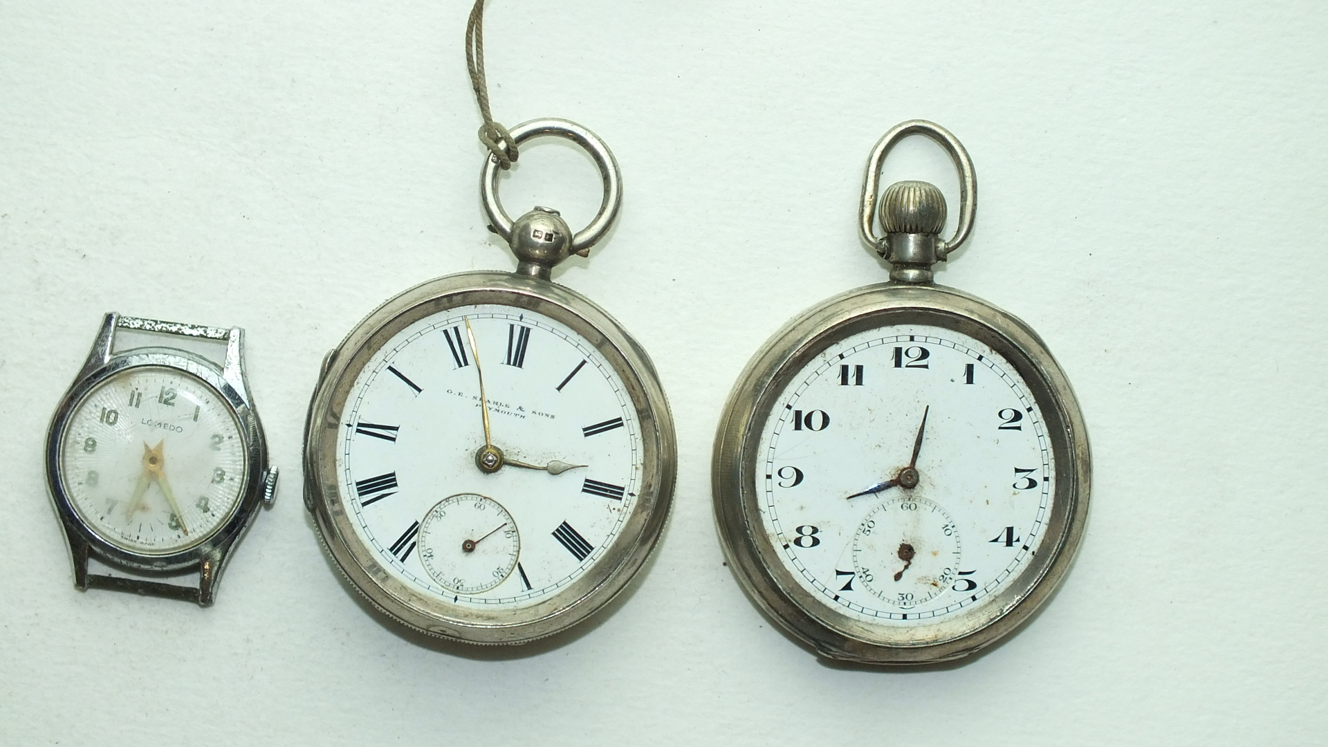 Lot 266 - Two silver-cased open-face pocket watches, (1 a/f) and a Lomedo wrist watch, (a/f), (3).