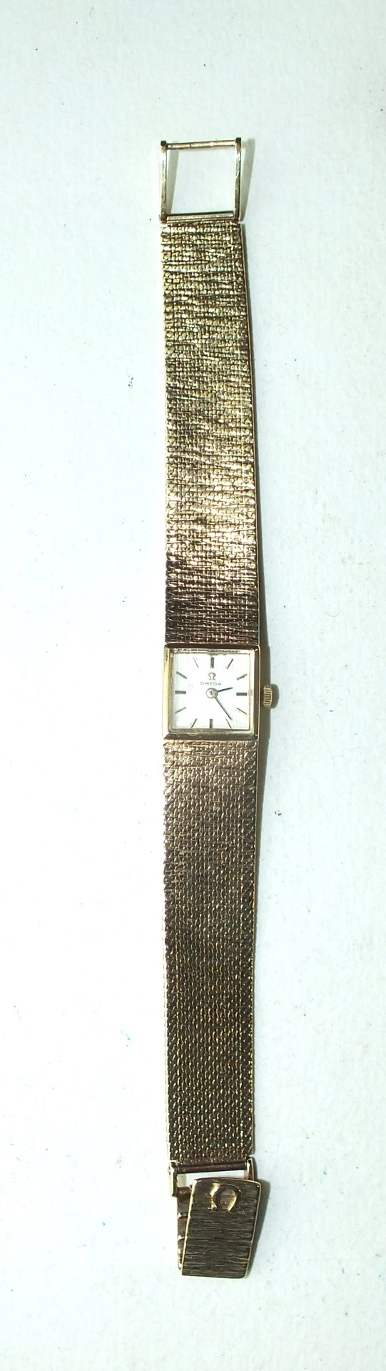 Lot 260 - Omega, a ladies 9ct gold wrist watch c1960's, the square dial with baton numerals, on slightly-