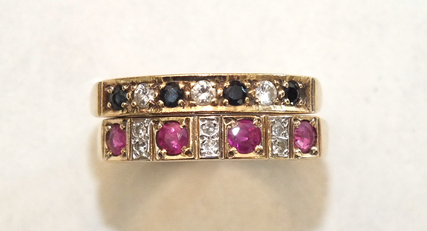 A ruby and diamond 9ct gold half-hoop ring, size Q½ and a similar sapphire and diamond ring, size