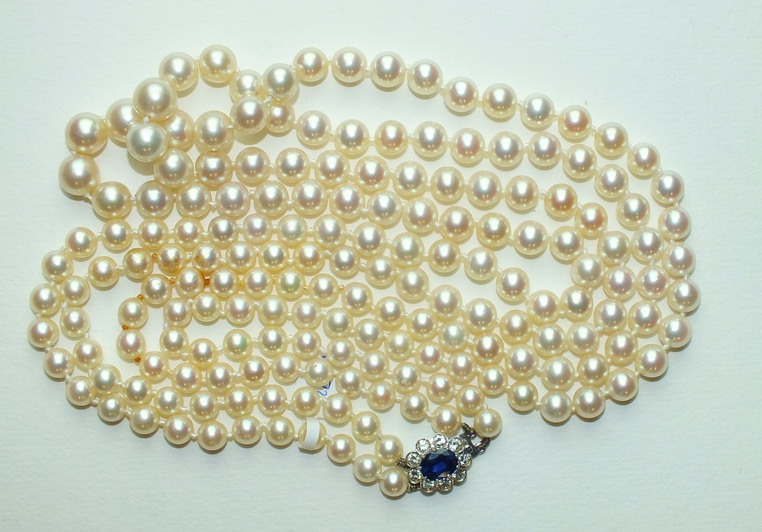 A long necklace of graduated cultured pearls, 6.5mm to 9.5mm, with 18ct white gold clasp set an oval