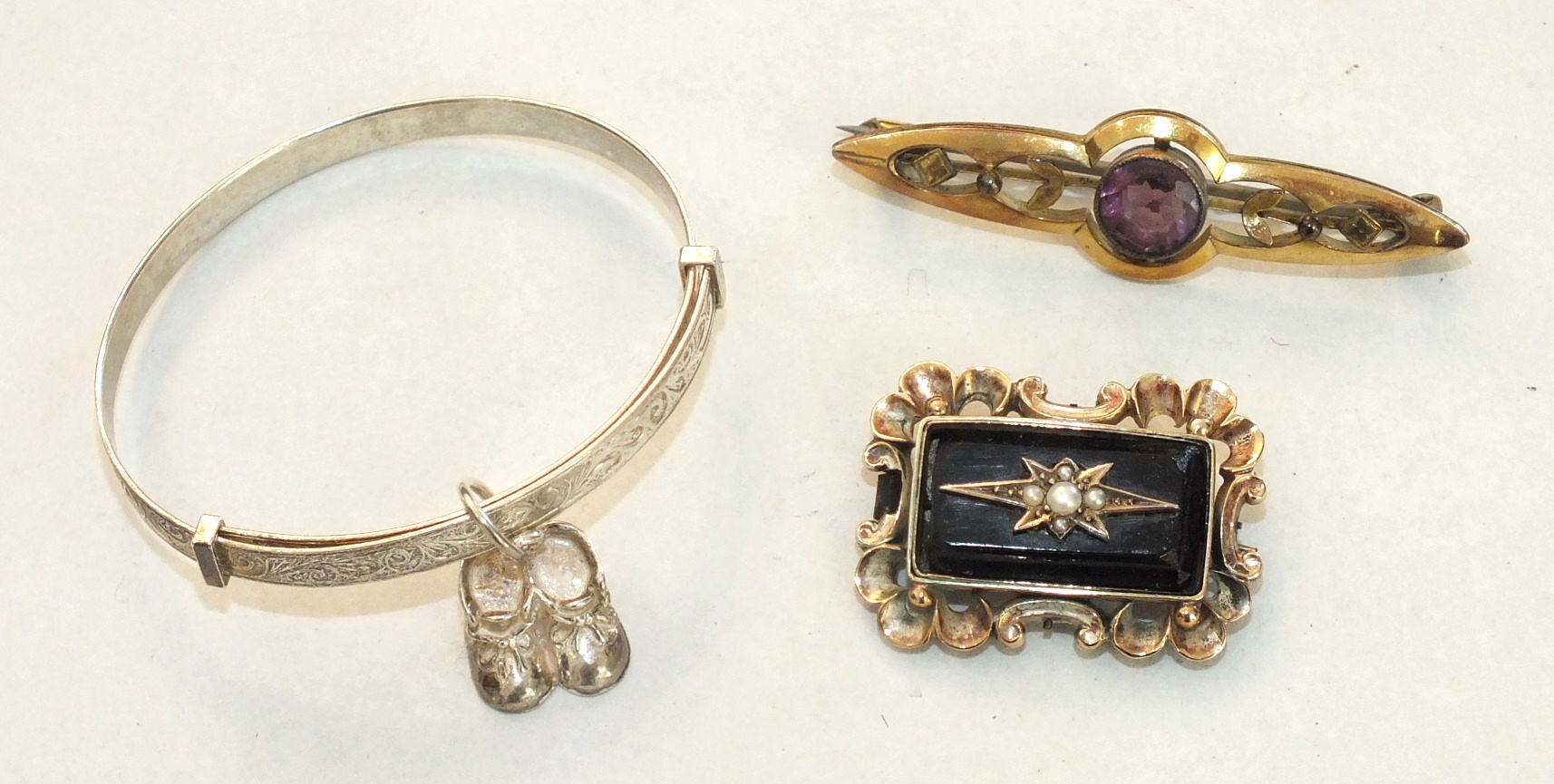 A Victorian mourning brooch with pearl-set onyx plaque within scrolling mount, another brooch and