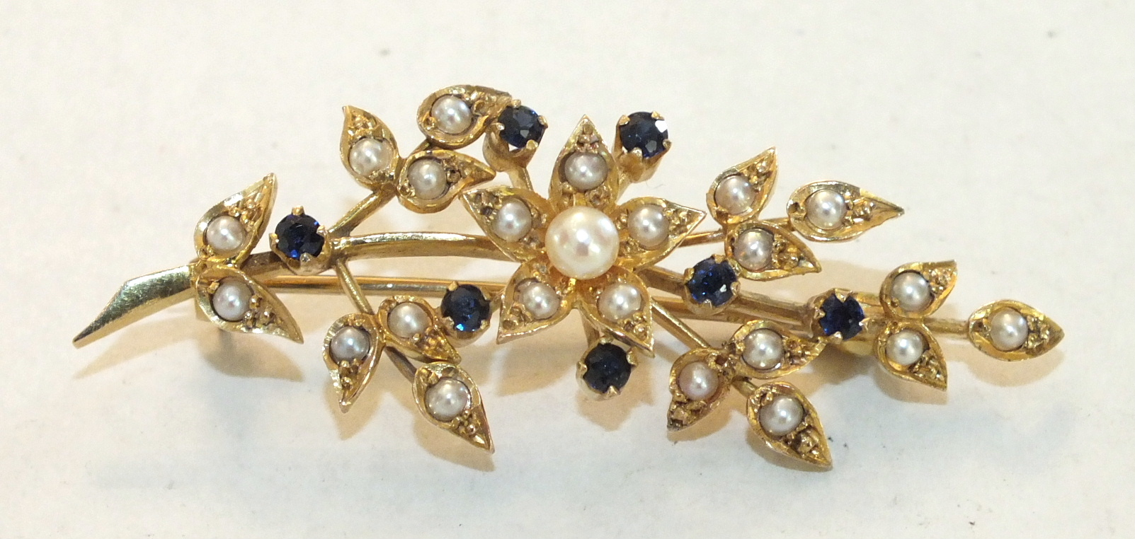 A sapphire and pearl spray brooch claw-set seven round-cut sapphires, amongst demi-pearl-set leaves,