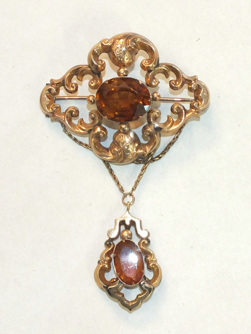 A Victorian brooch of scrolling form set oval citrine, with similarly-set drop below and later