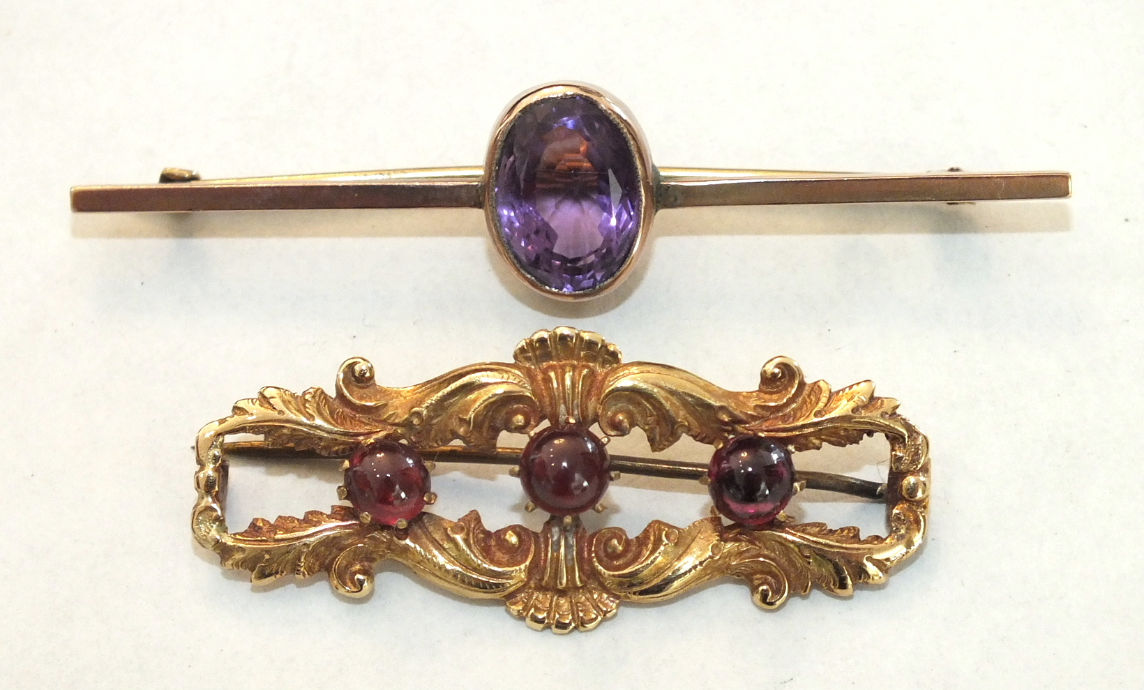 A 9ct gold bar brooch collet-set an oval amethyst, 3.9g and a yellow metal brooch set three garnets,