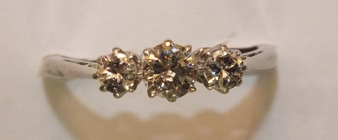 A three-stone diamond ring, the claw-set brilliant-cut diamonds totalling approximately 0.6cts, in - Image 2 of 2