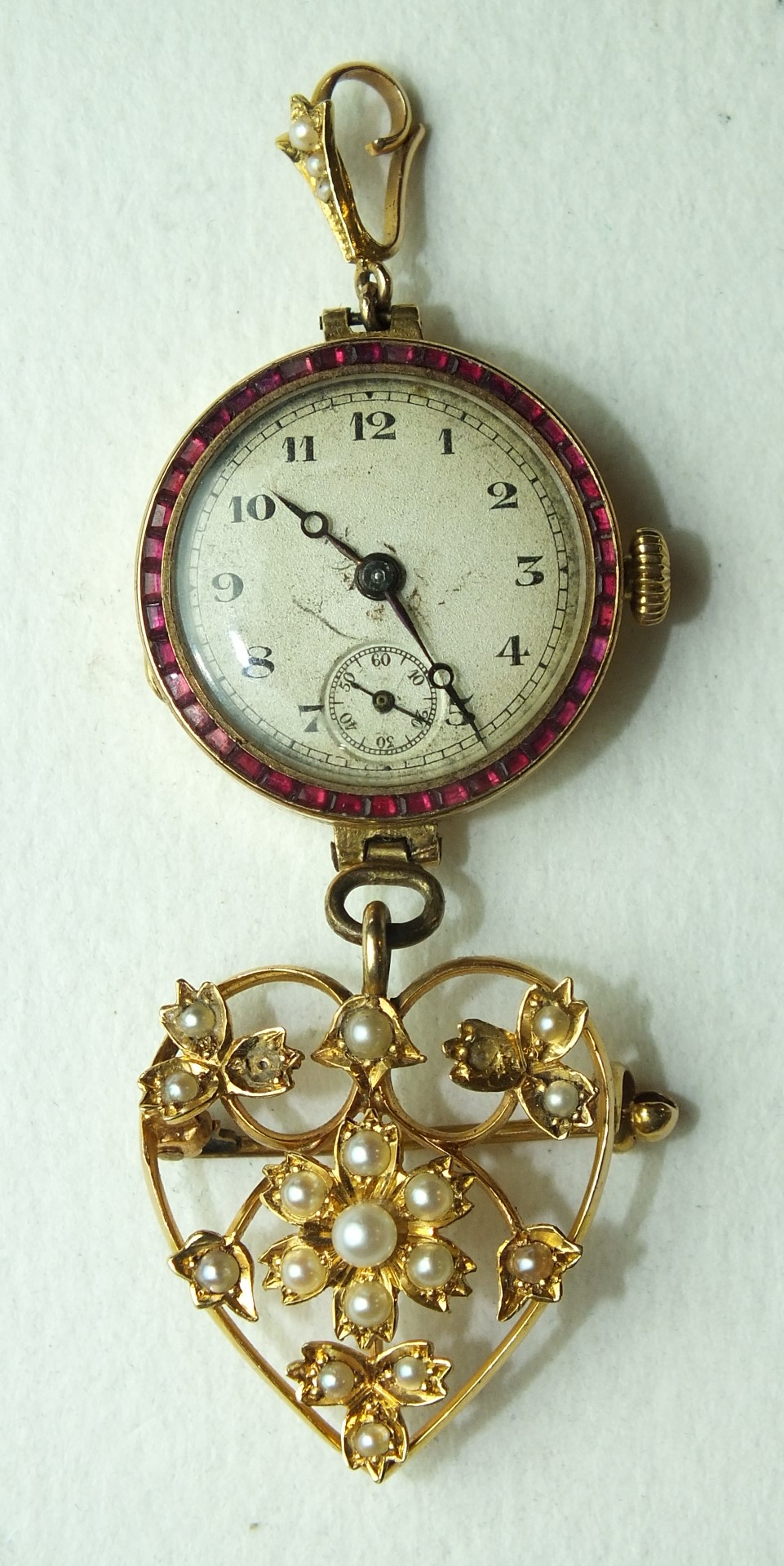 Lot 192 - An 18ct-gold-cased wrist watch, (not working), with ruby-set bezel mounted as a fob watch, with a