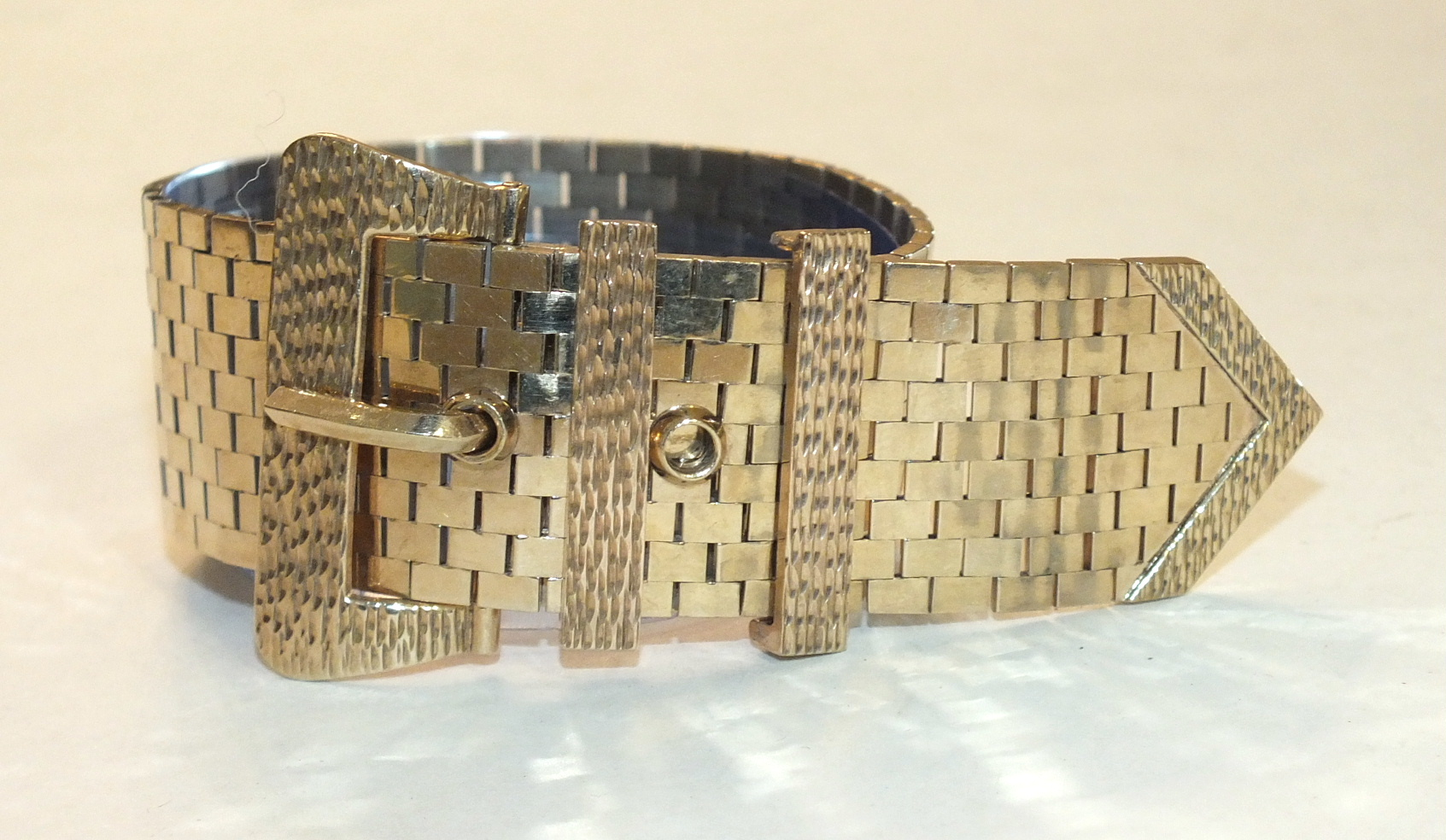 A 9ct gold brick-link wide bracelet in the form of a belt and buckle, with textured buckle and two
