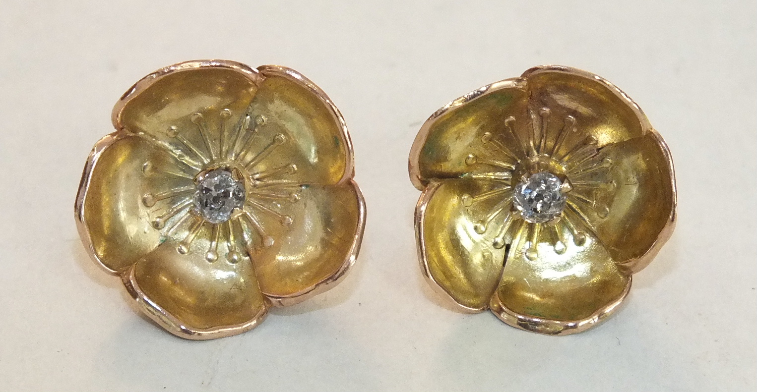 A pair of gold earrings in the form of poppy flowers, each centrally-set an old brilliant-cut