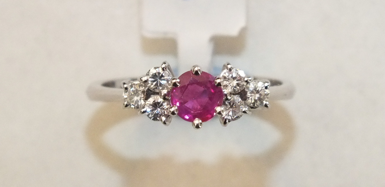 A ruby and diamond cluster ring claw-set a round-cut ruby between two triplets of brilliant-cut
