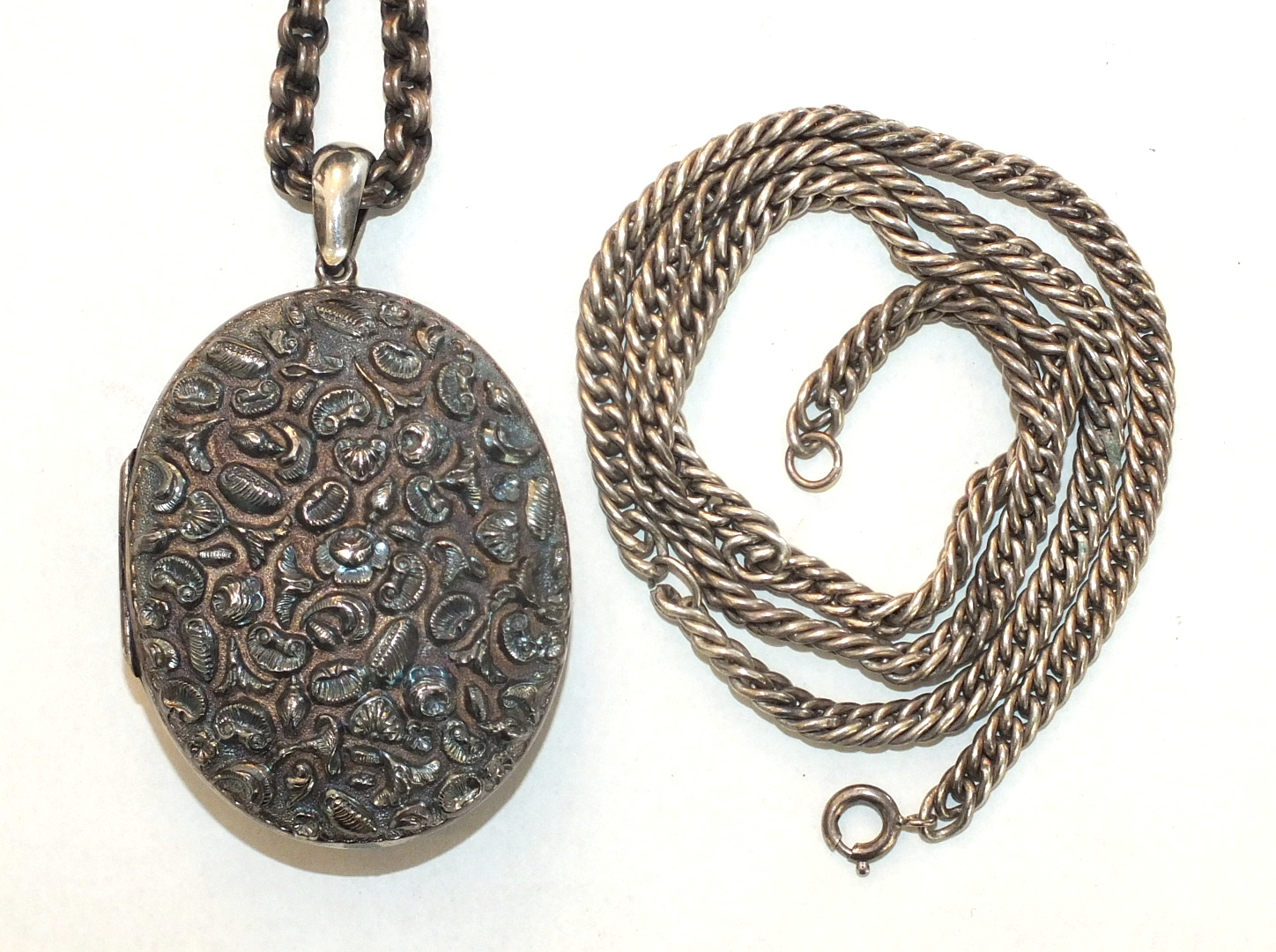 A large white metal locket embossed on both sides with flowers, leaves and shells, and two