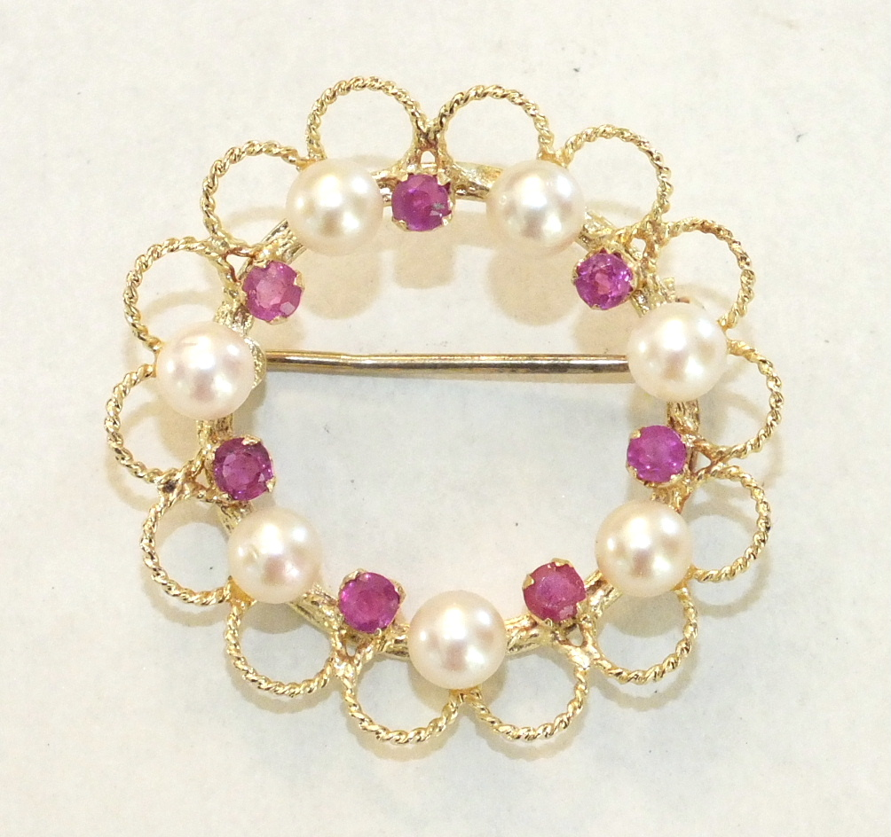 A modern circle brooch, alternately-set seven each round-cut rubies and cultured pearls, within