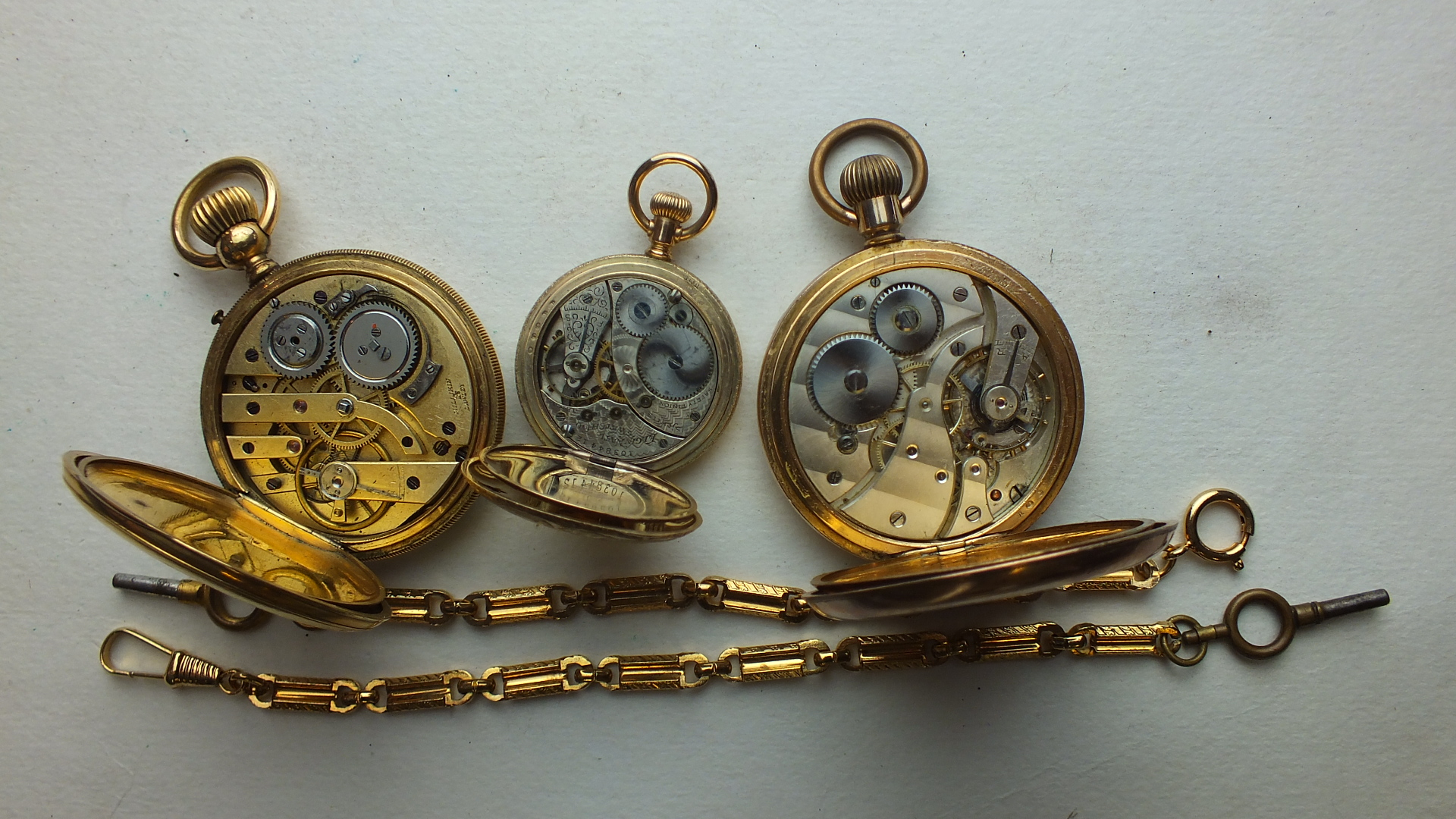Lot 244 - Three gold-plated keyless open-face pocket watches, (all a/f) and two plated watch chains, (5).