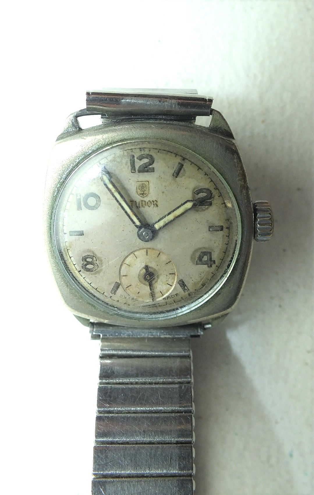 A vintage Tudor cushion-cased wrist watch, the silvered dial with Arabic and baton numerals and
