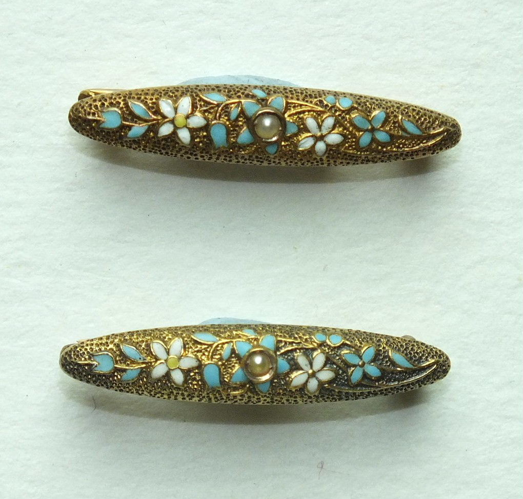 A pair of small 14k gold brooches, each set a seed pearl within enamelled floral decoration, 24mm