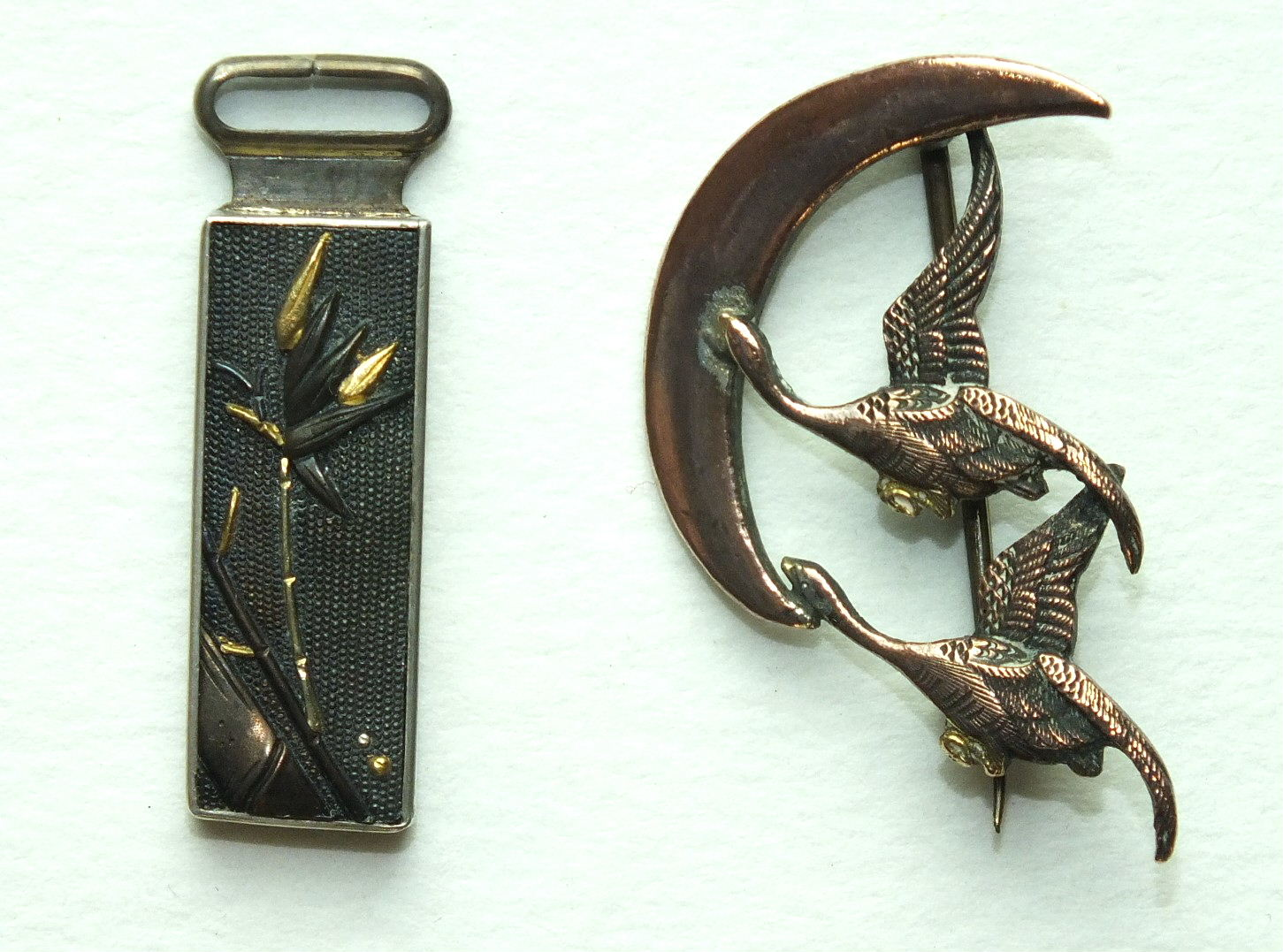 A small oblong Skakudo pendant with bamboo decoration, 32mm long and a brooch in the form of two