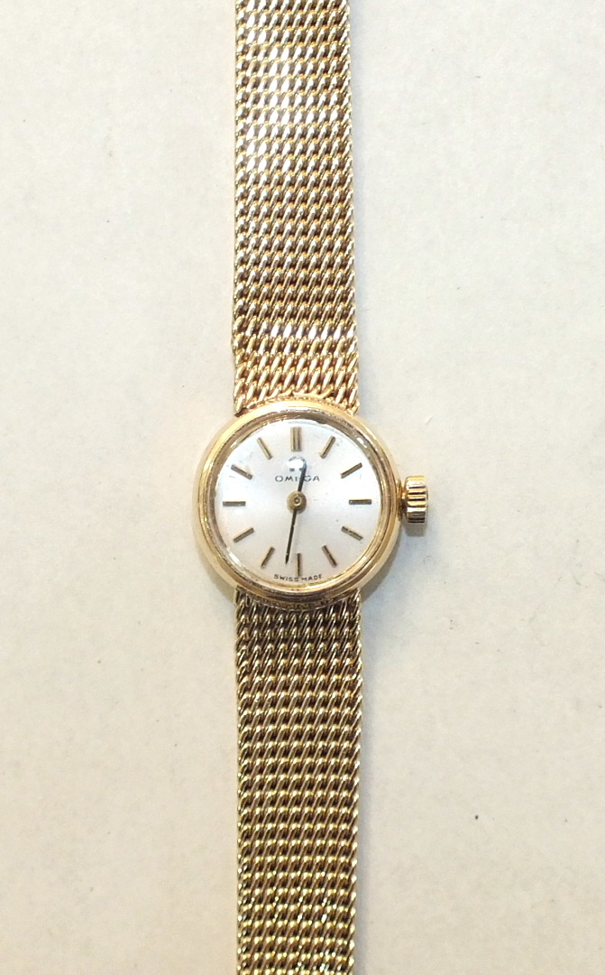 Lot 264 - Omega, a ladies 9ct-gold-cased round-faced wrist watch, the silvered dial with baton numerals, on