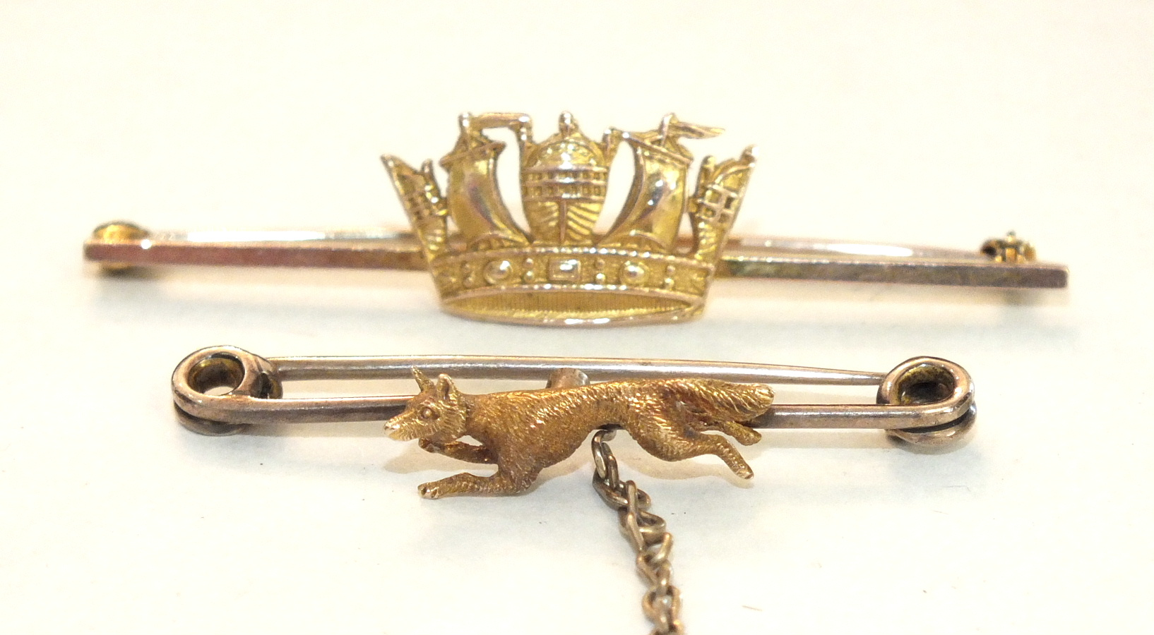 A small hunting brooch with a running fox, unmarked, 3.8cm long and a Naval crown sweetheart brooch,