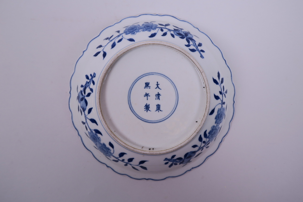Lot 10 - A Chinese blue and white porcelain dish with lobed rim, decorated with a dragon and phoenix