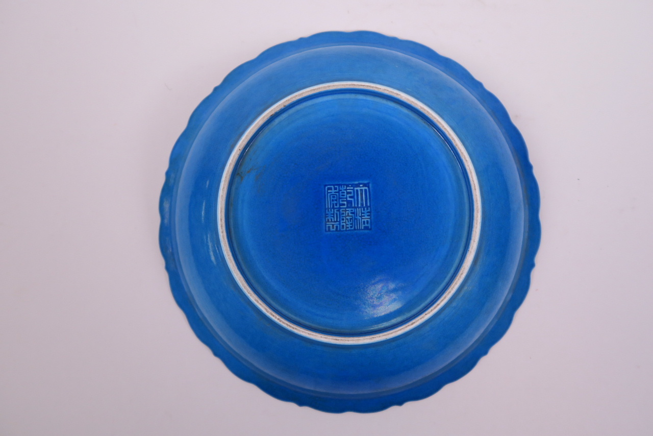 Lot 15 - A Chinese blue glazed dish with petal shaped rim and incised decoration of storks in flight,