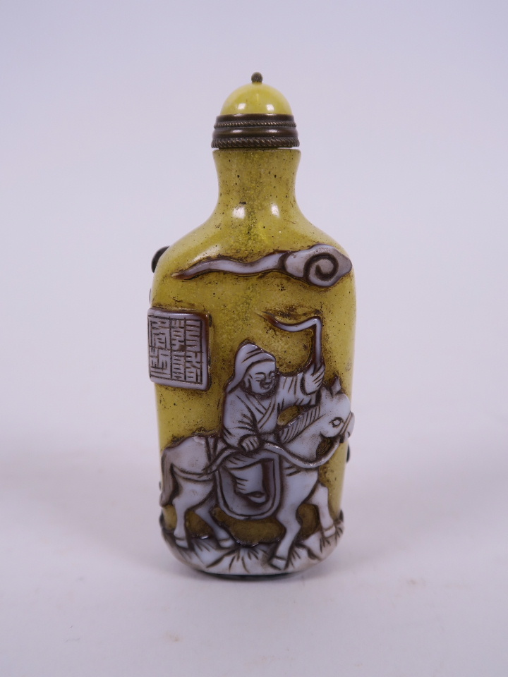 "Lot 14 - A Peking glass snuff bottle, with decoration of travelling figures, 3½"" high"