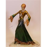 A contemporary Art Deco style figure, woman in a green dress (A/F loss to thumb), mounted on an onyx
