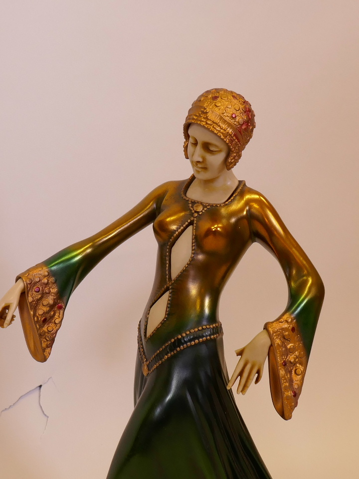 Lot 46 - A contemporary Art Deco style figure, woman in a green dress (A/F loss to thumb), mounted on an onyx