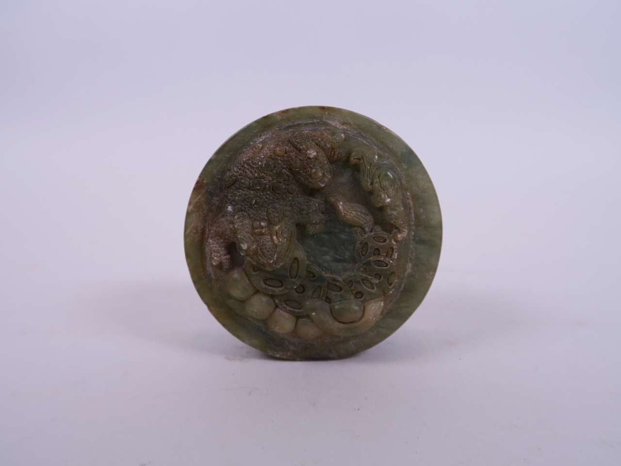"""Lot 39 - A Chinese mottled hardstone cylinder seal with carved decoration to the top of Chan Chu, 2"""" diameter"""
