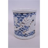A Chinese blue and white porcelain brush pot with raised decoration of a dragon and carp,