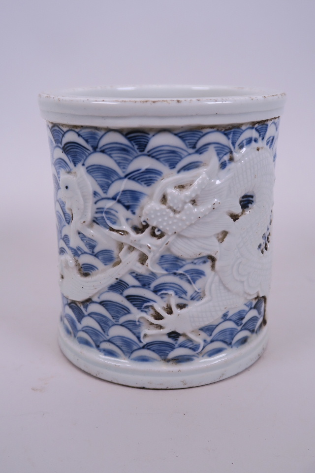 Lot 40 - A Chinese blue and white porcelain brush pot with raised decoration of a dragon and carp,