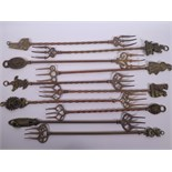 A collection of ten brass toasting forks, the handles cast with various town and country
