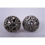 A pair of Chinese white metal meditation balls with pierced dragon and phoenix decoration, 2""