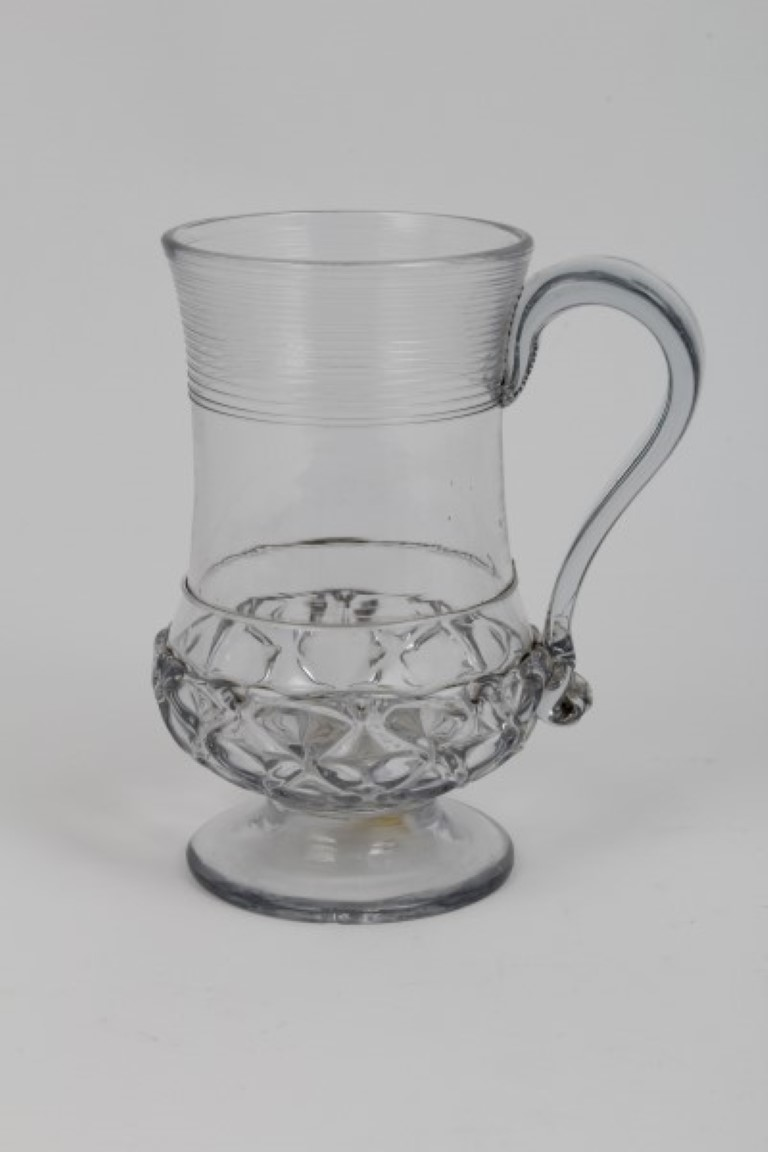 Lot 8 - Georgian glass baluster-shaped mug with trailed and moulded decoration, the base inset with a George