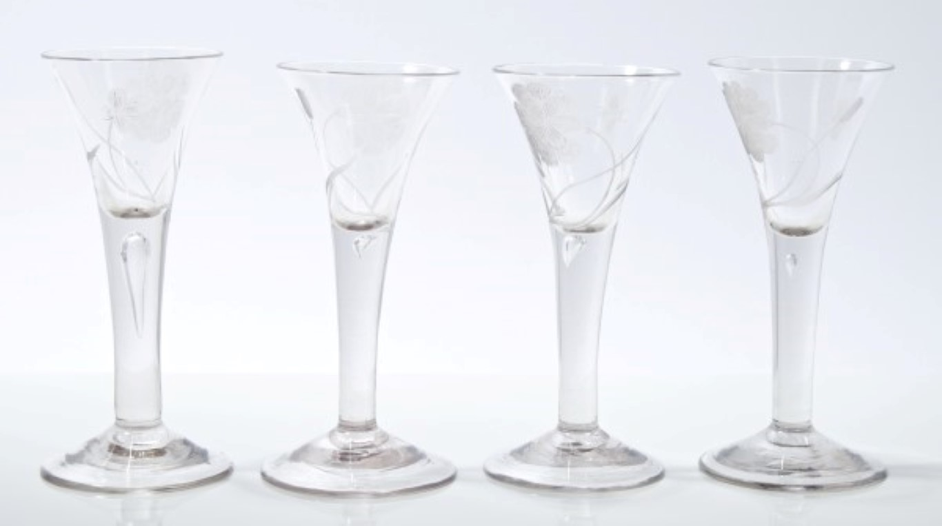 Lot 7 - Set of four Georgian wine glasses with trumpet-shaped bowls, each engraved with flower and insect,