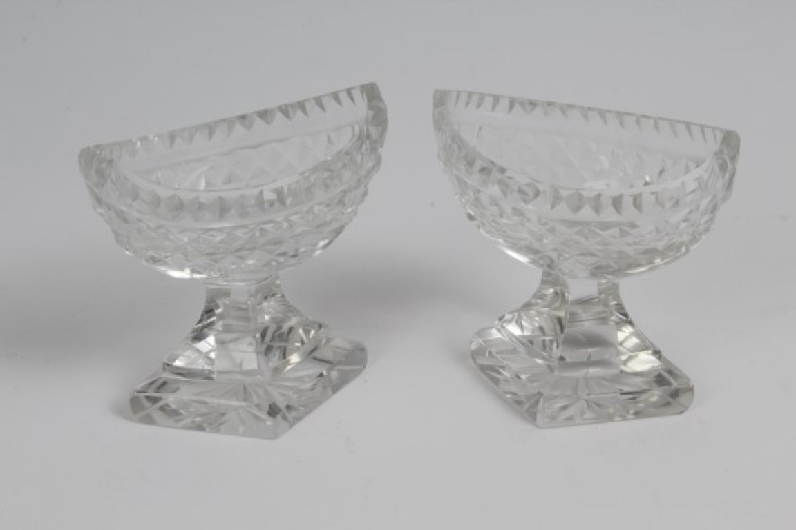 Lot 18 - Pair George IV cut glass boat-shaped salts on diamond-shaped stepped bases