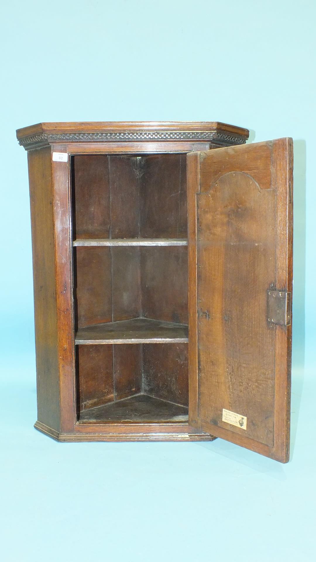 Lot 82 - A small Georgian oak hanging corner cupboard, the panelled door with inlaid star motif, 63cm wide,
