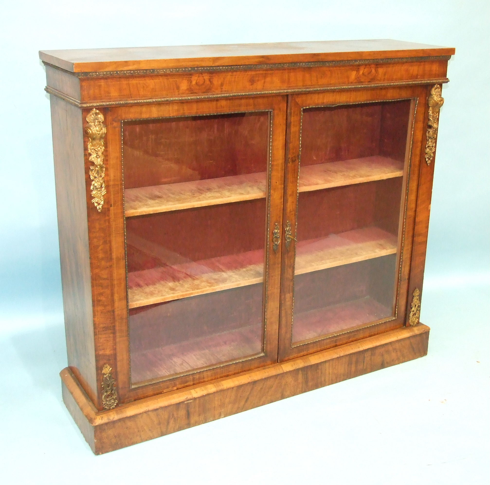 Lot 104 - A Victorian walnut side cabinet, the rectangular top above a pair of plain glazed doors, on plinth