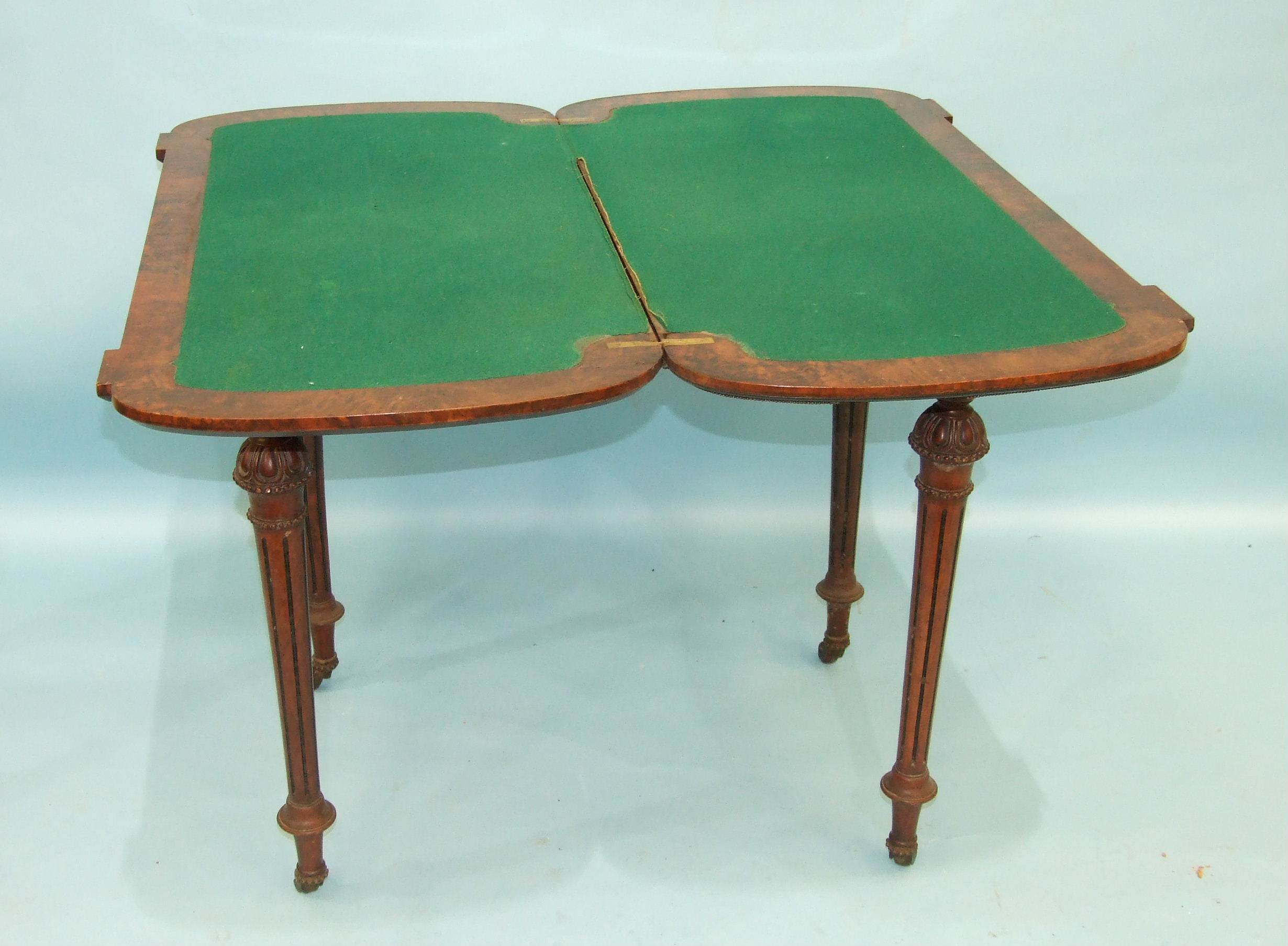Lot 97 - A Victorian burr walnut card table, the fold-over top with metal beaded border raised on carved