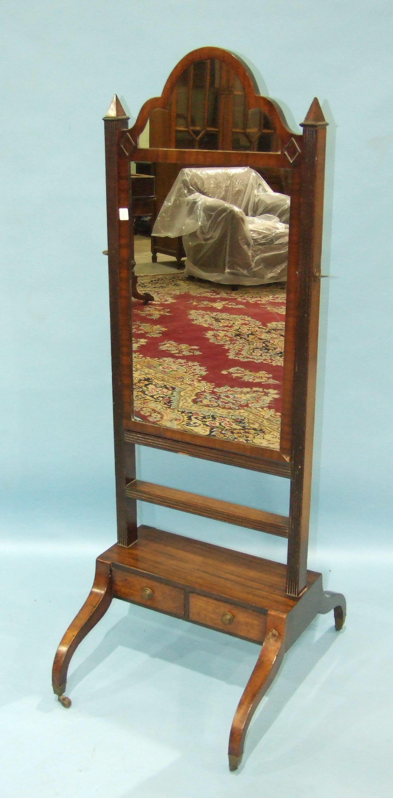 Lot 91 - An early-19th century mahogany cheval mirror, the arch plate within reeded frame to the base