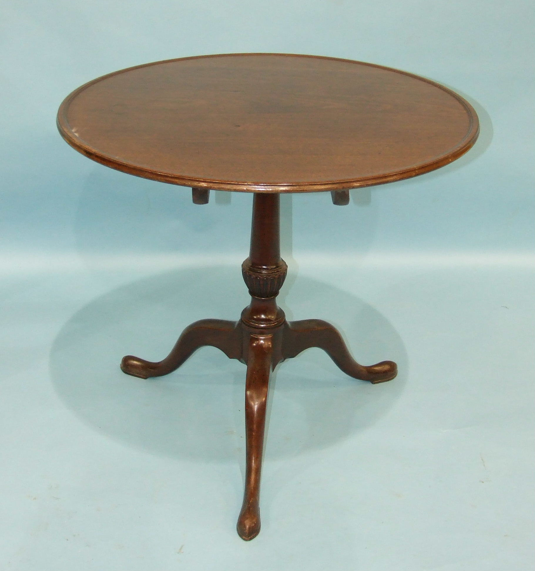 Lot 81 - An 18th century mahogany tripod table, the circular top with moulded border, on carved and turned