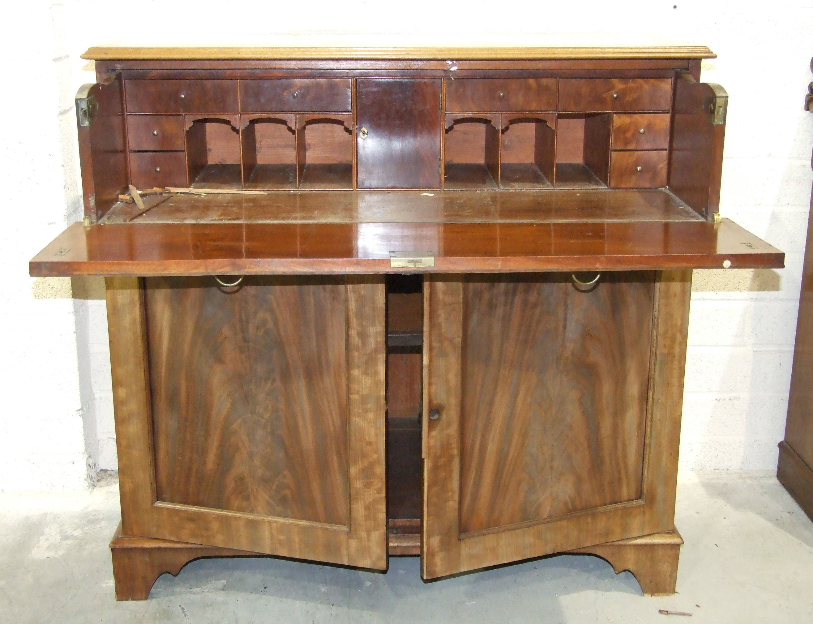 Lot 83 - An early-19th century mahogany secretaire writing chest, the fitted drawer above a pair of