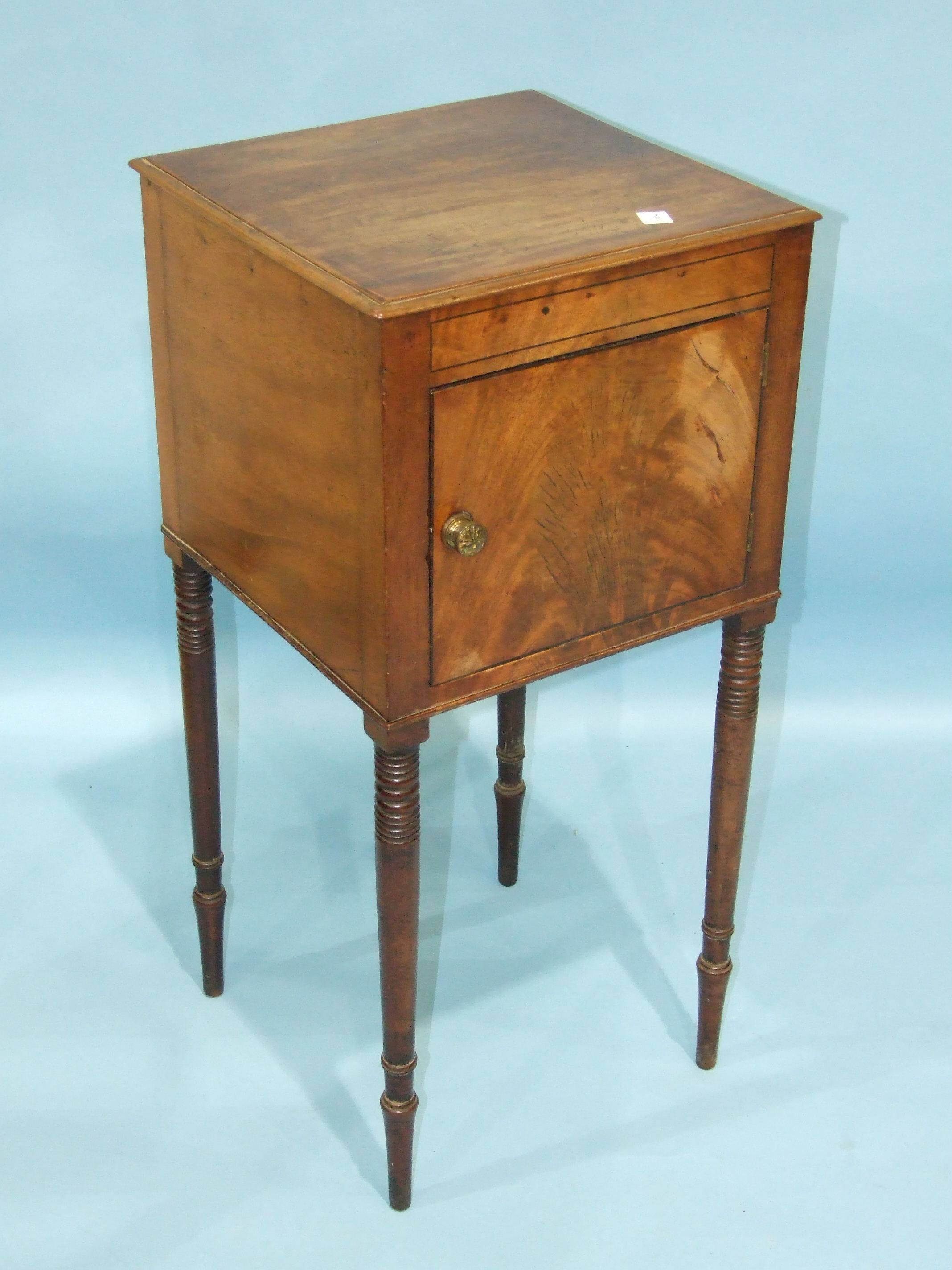 Lot 74 - A Georgian mahogany pot cupboard having a hinged door, on ring-turned tapered legs, 37cm wide,
